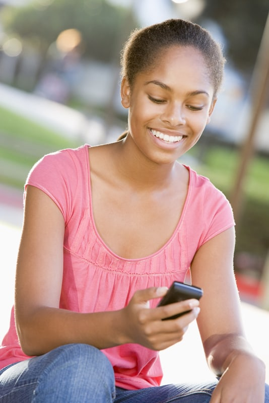 Teenage Girl Sitting Outdoors Using Mobile Phone